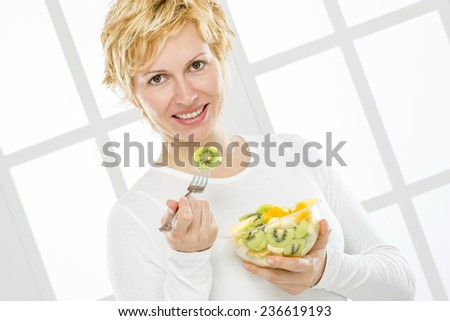 Forty years old woman eats fruit meal - stock photo