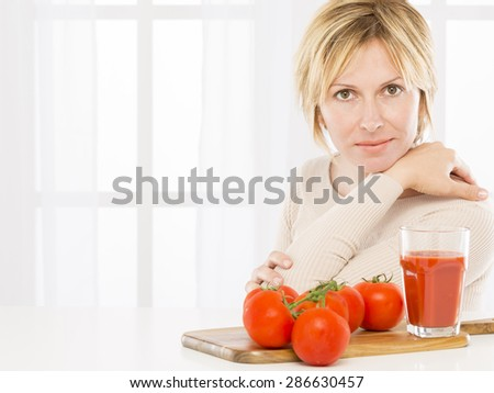 Forty years woman and tomatoes - stock photo
