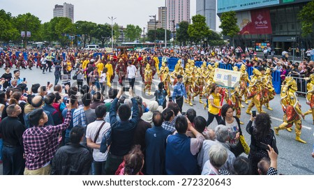 FOSHAN Apr 21:Birthday, Taoist god believers dressed in traditional clothing, carried the gods, patrol, residents along the way to watch and took out his camera phone  April 21, 2015 in Foshan, China - stock photo