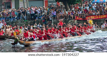 FOSHAN, CHINA - JUNE 3:The dragon boat competition held in Fenjiang River, 17 dragon boat to participate, attracting a large number of people to watch, Qingyun team won the first June 3, 2014 in Foshan, China - stock photo
