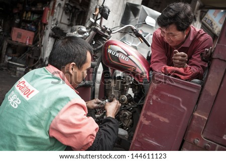FOSHAN, GUANGDONG/CHINA - MARCH 16: Unidentified garage mechanic works on motorcycle as customer watches in Shunde District of Foshan City, Guangdong Province, China on March 16th, 2013.  - stock photo