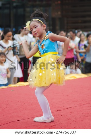 FOSHAN -MAY 1:To celebrate the international labor day and entertaining, kindergarten children in city centres perform a dance on the stage, get the welcome of people May 1, 2015 in Foshan, China - stock photo
