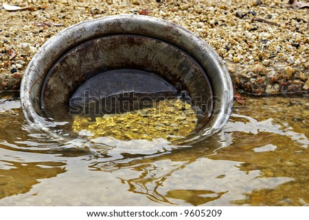 found it golden nuggets  gold pan in the water - stock photo