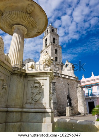 Fountain and ancient church tower in the touristic landmark of San Francisco Square in  Old Havana - stock photo