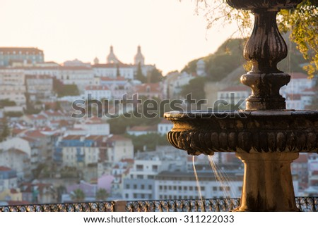 Fountain at a miradouro in Lisbon, capital of Portugal, lit by the first yellow light of the sun with church and fortress in the distance blurred by background blur leaving room for copy space - stock photo