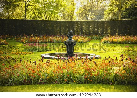 Fountain in evening golden light. Park sculpture. Boy and frog in the pond of  Queen Mary's Garden in  Regent's park, London, UK.  - stock photo