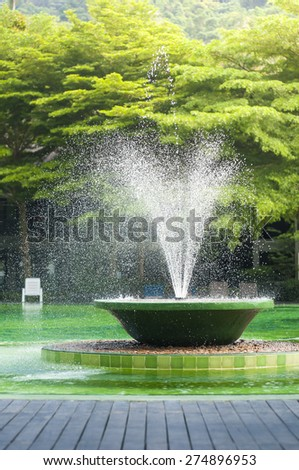 Fountain in fresh summer green pool. - stock photo