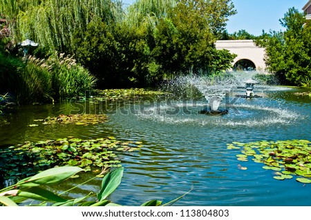 Fountain in middle of a water garden of lily pads and other water plants. - stock photo