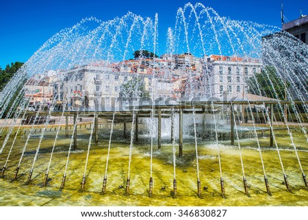 Fountain in the center of the city. Romantic Lisbon street with the typical old buildings and new buildings - stock photo