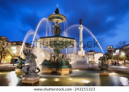 Fountain on Rossio Square at night in Lisbon, Portugal. Baroque style artwork with mythical creatures sculptures. Column of Dom Pedro IV in the background. - stock photo
