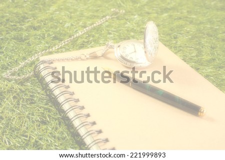 fountain pen and pocket watch on book,soft focus - stock photo