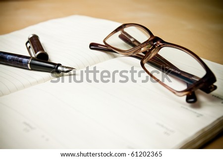 Fountain pen glasses and calendar in composition in color - stock photo