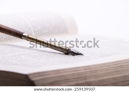 Fountain pen on an antique old book - stock photo