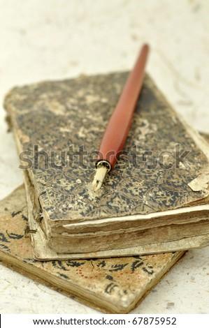 Fountain pen on grunge old books - stock photo