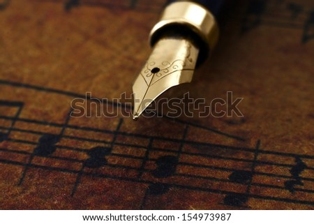 Fountain pen on music sheet - stock photo