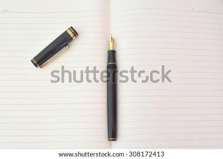 Fountain pen on notebook - stock photo