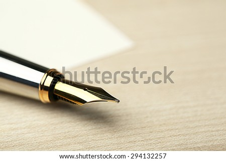 Fountain pen on white sheet of paper and wooden table background - stock photo