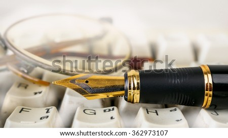 Fountain pen  shot with shallow depth of field on white dirty keyboard - stock photo