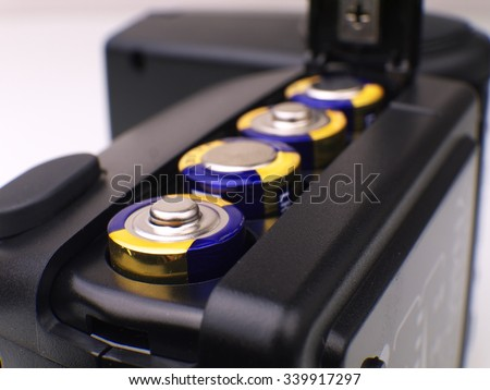 four AA batteries in battery compartment, macro, shallow depth of field - stock photo