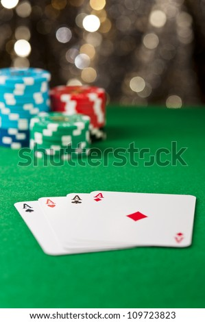 Four ace on a poker table with chips in front of a gold glitter background - stock photo