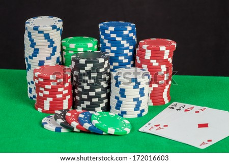 Four Aces and poker chips stack on green table - stock photo