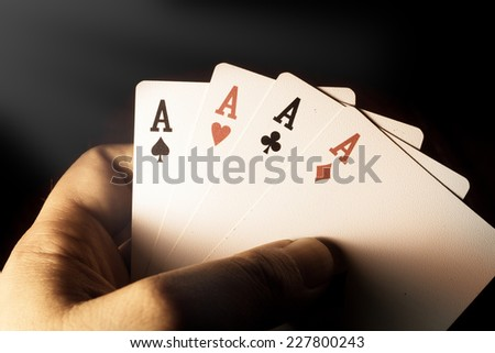 Four Aces cards in hand for play gamble,vintage filtered.  - stock photo