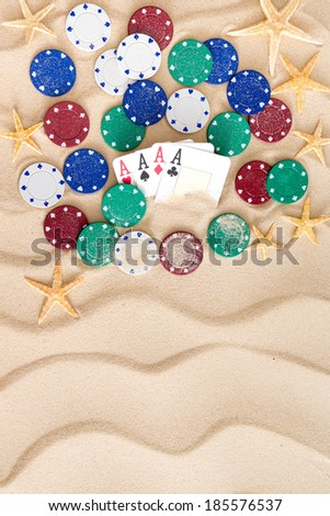 Four aces surrounded by poker chips and scattered starfish on golden beach sand with a decorative wavy pattern and copy space - stock photo