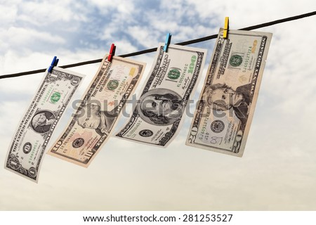 Four american dollars drying on string with sky and trees in the background - stock photo
