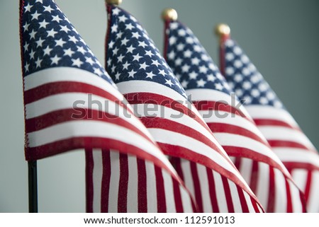 Four American flags stand in a row. - stock photo