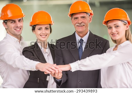 Four architects putting hands together while looking at camera. Team work concept. - stock photo