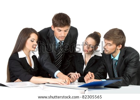four attractive positive young business people in elegant suits sitting at desk working in team together and discussing the problem, business plan, papers, document, Isolated over white background - stock photo