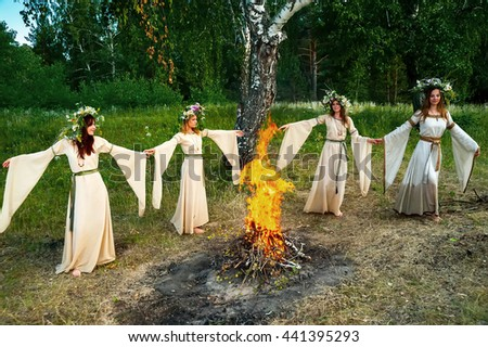 Four attractive Women with Wreath of Flowers dancing around bonfire. Ivan Kupala Holiday Celebration. Russia - stock photo