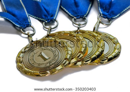 Four award medals of gold color with the number 1 and blue ribbons isolated on a white background - stock photo