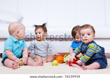 Four babies group sitting on the floor - stock photo
