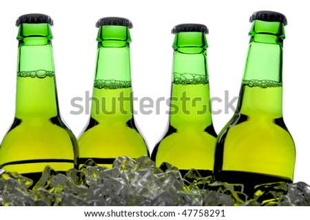 Four Backlit Beer Bottles Green and Brown Standing in Ice with Condensation and Reflection in foreground - stock photo