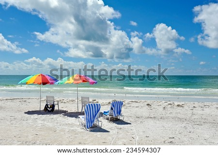 Four Beach Chairs with Colorful Umbrellas on the Beach - stock photo
