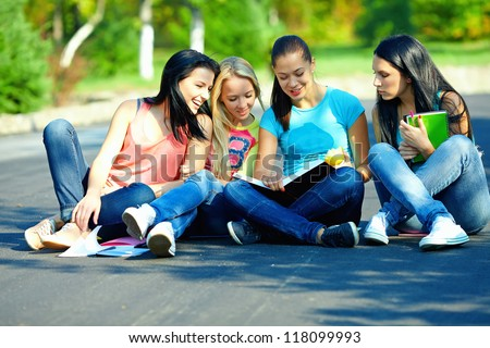 four beautiful girls friends read books, sitting on the ground - stock photo