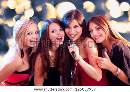Four beautiful stylish girls singing karaoke at the club - stock photo