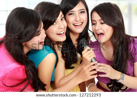 Four beautiful stylish woman singing karaoke together - stock photo