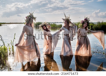 Four beautiful women with wreath of flowers enter in lake water (Ivan Kupala Holiday Celebration) - stock photo