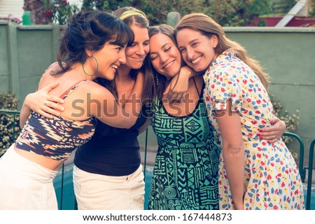 Four best friends hugging each other - stock photo