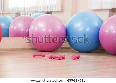 Four Big Fitballs and Barbells On Floor in Sport Fitness Center Indoors. Horizontal Image Orientation - stock photo