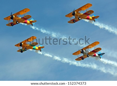 Four Biplanes Flying in Formation with Smoke - stock photo