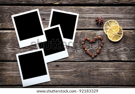 Four blank instant photo frames with coffee beans in shape of a heart on old wooden background. - stock photo