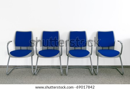 Four Blue chairs in simple empty waiting room - stock photo