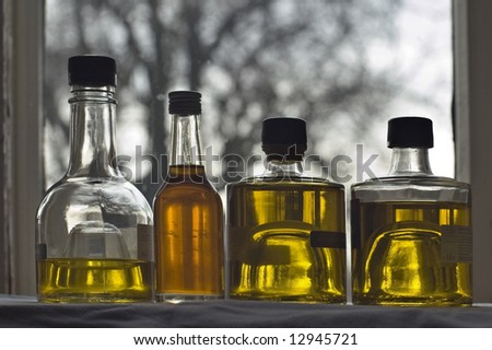 Four bottle of olive oil at the window - stock photo