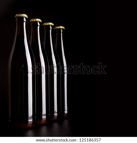 Four bottles of beer on a black background - stock photo