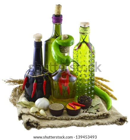 Four bottles with peppers and spices on burlap bags isolated - stock photo
