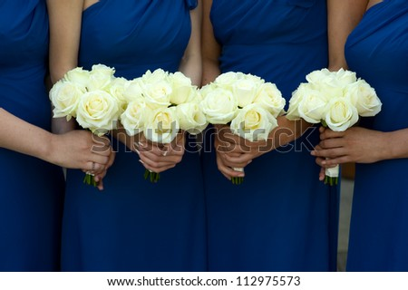 four bridesmaids in blue dresses holding white rose bouquets - stock photo