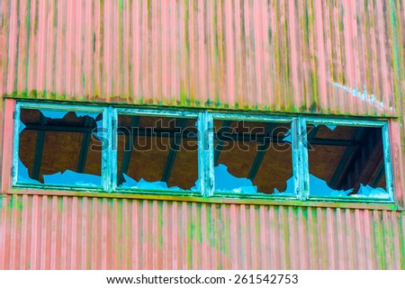 Four broken windows in a row on old industrial building. Wall is metal with red paint and lots of green moss. Blue sky reflected in glass. Inside roof visible in holes. - stock photo